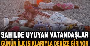 Sahilde uyuyan vatandaşlar günün ilk ışıklarıyla denize giriyor